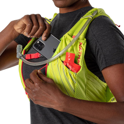 NATHAN Pinnacle 12 Liter Women's Hydration Race Vest - Finish Lime/Hibiscus Red - Female Runner Pulling Cell Phone/Smartphone From Front Pocket