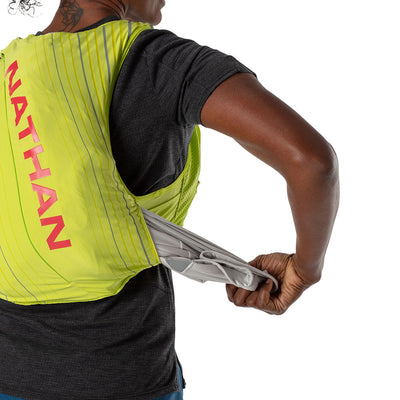 NATHAN Pinnacle 12 Liter Women's Hydration Race Vest - Finish Lime/Hibiscus Red - Female Runner Pulling Clothing From Easy-Access Kangaroo Pocket