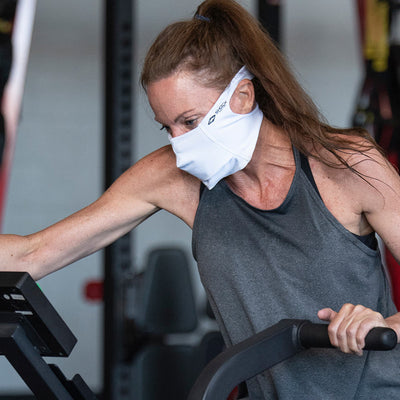 White Play Safe Face Mask Lifestyle Image – Female Model Wearing Protective Safety Face Mask in the Gym while on an Elliptical - Left Angle