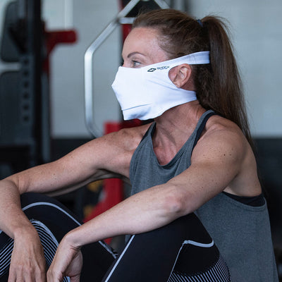White Play Safe Face Mask Lifestyle Image – Female Model Wearing Protective Safety Face Mask in the Gym while Sitting Down - Left Angle