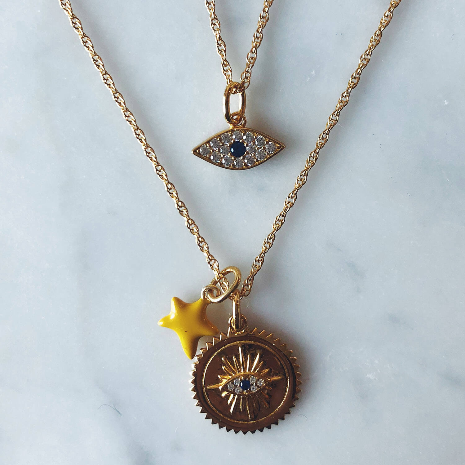 Evil Eye Charm in Gold Vermeil on table