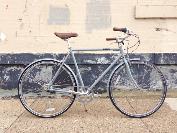 Grey bicycle with brown saddle and grips