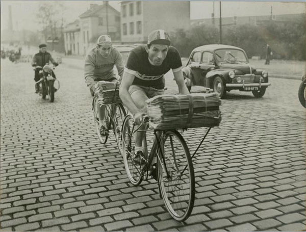 old photograph of man transporting newspapers on bicycle
