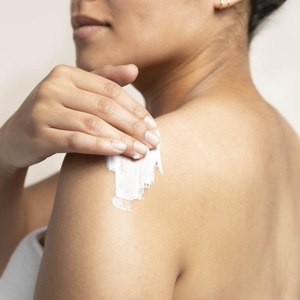 Woman applying LATHER Lavender Lime Moisturizer to her shoulder