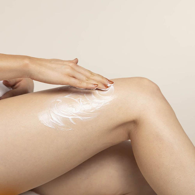 Woman applying LATHER Lavender Lime Moisturizer to her thigh