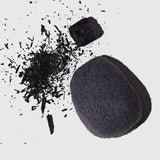 Charcoal Konjac Facial Sponge next to a shattered chunk of charcoal