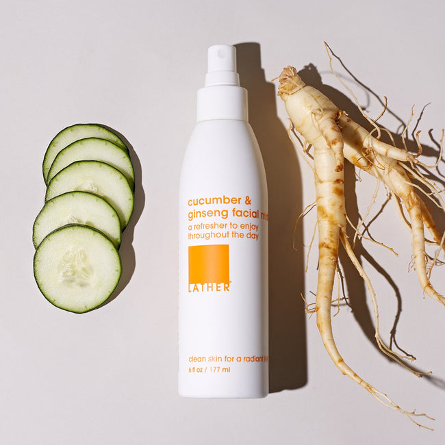 Cucumber and Ginseng Facial Mist bottle next to slices of cucumber and a raw ginseng root