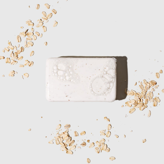 Exfoliating Body Soap with Oatmeal and Bamboo Extract. Sudsy soap surrounded by artfully sprinkled oatmeal.