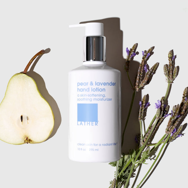 Pear and Lavender Hand Lotion bottle surrounded by sliced pear and sprigs of lavender