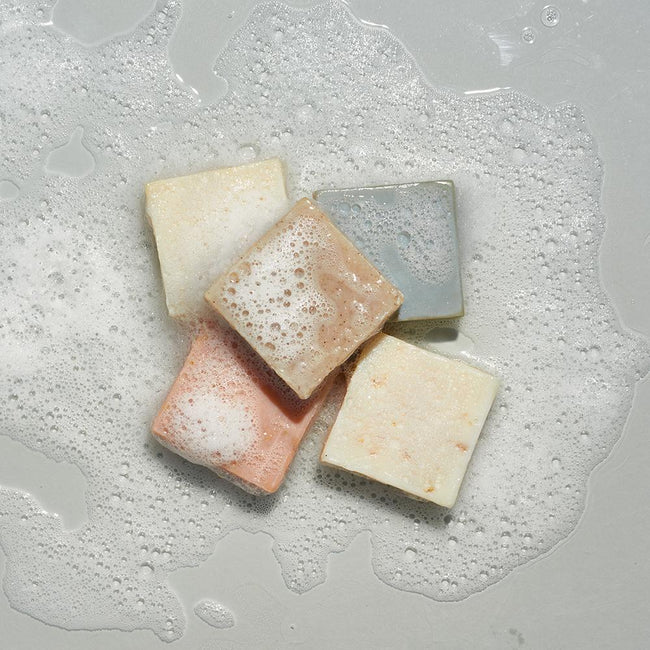 Variety of LATHER bar soaps in sudsy water