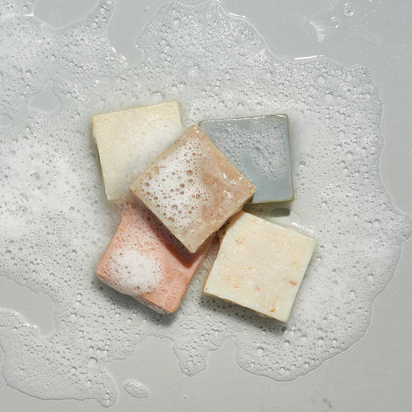 LATHER bar soaps stacked in a sudsy puddle of water