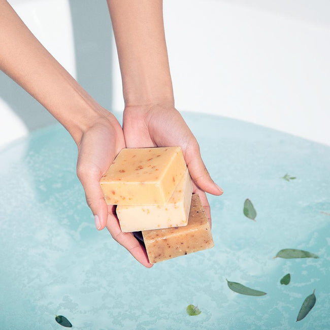 Model hands holding three stacked bars of LATHER soap over a bathtub full of clear blue water.