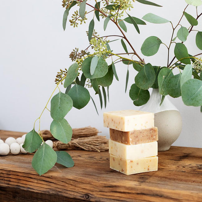Stack of four LATHER soap bars next to a vase filled with eucalyptus branches