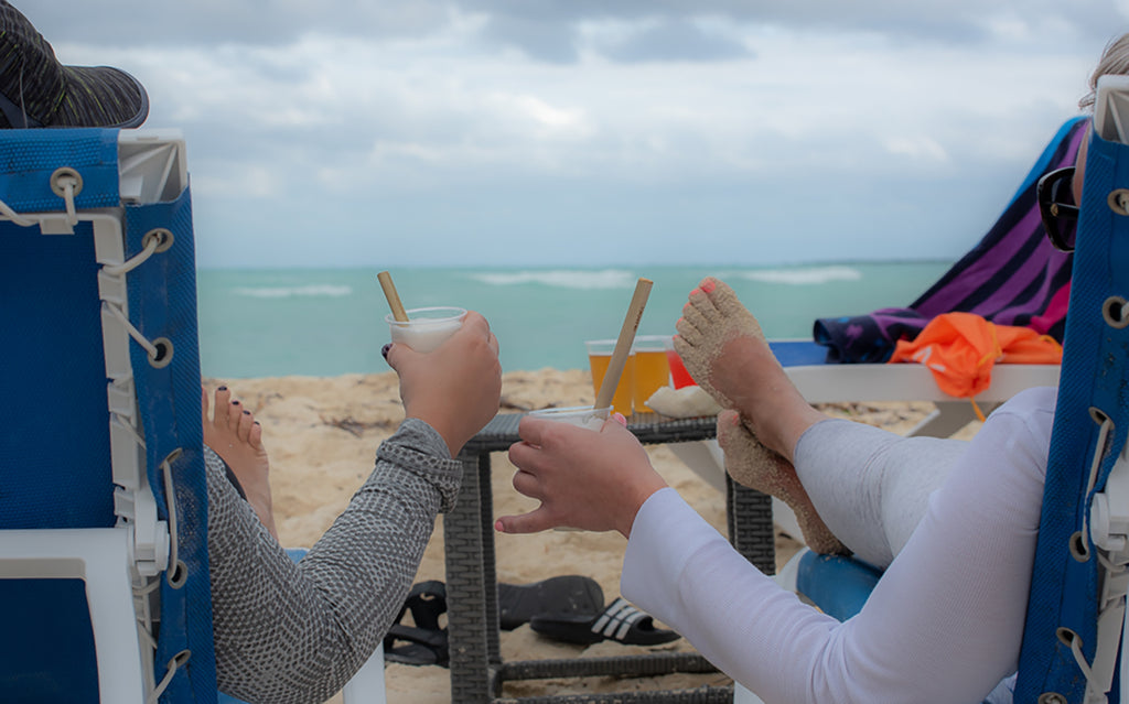 Having drinks on a beach with reusable bamboo straws