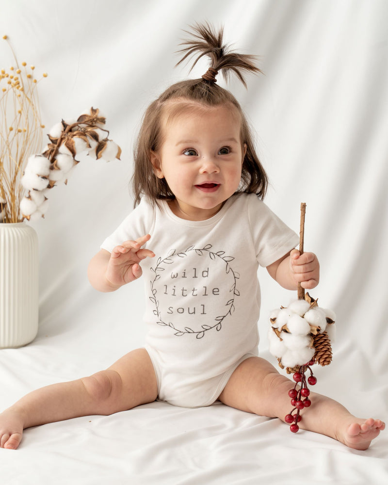 "Short sleeve unisex baby bodysuit, featuring a hand-draw spring wreath and a slogan ""wild little soul"" at the front.  Envelope neckline design and snap buttons for effortless dressing and nappy changing."