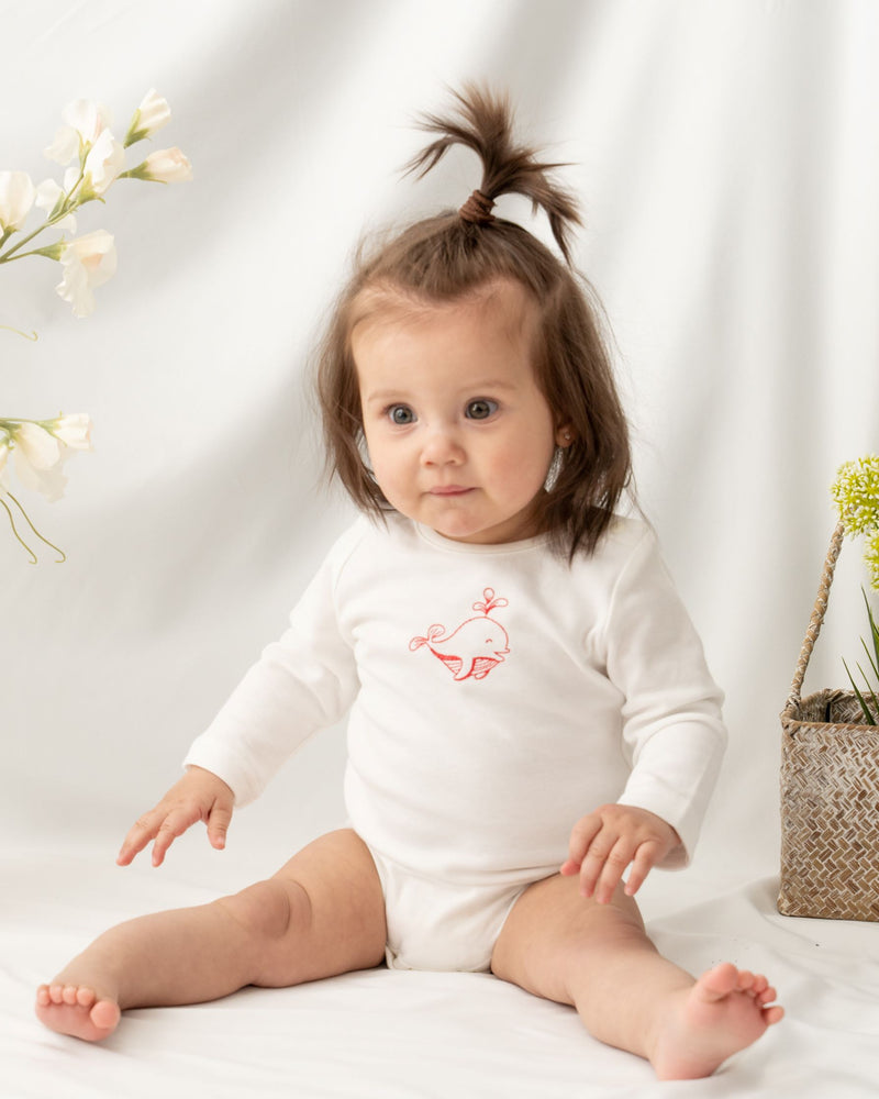 Baby girl wearing long sleeve white color unisex baby bodysuit, featuring a hand-draw cute little dolphin embroidered at the front. Snap buttons on the left shoulder and bottom for effortless dressing and nappy changing.
