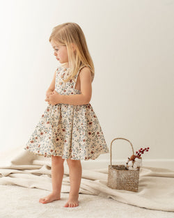 Baby girl dressing Organicline floral pinafore dress. Made from 100% certified organic cotton.