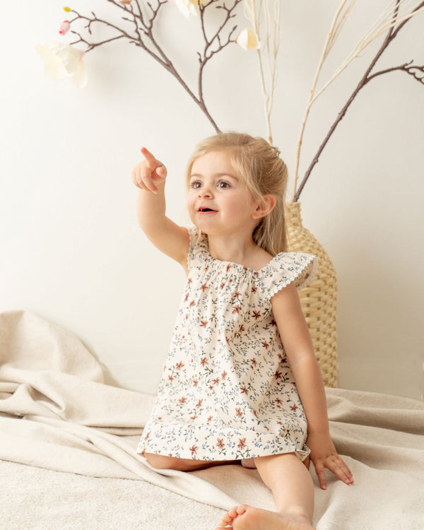 Little girl wearing Organicline Floral A-Line dress. Featuring angle-sleeves with baby lace eyelet on the edge and a gentle elastic square neckline, our softly made floral print pattern dress offers a classic look in vintage style.