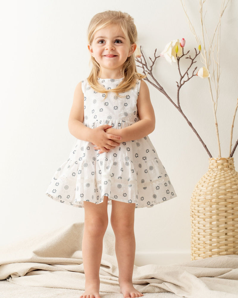 Little girl dressing Organicline Sweetheart dress, softly made from organic cotton in woven , featuring abstract chamomile flower pattern on natural white. Unique lace eyelet embroidered on the  ruffled dress hemline.