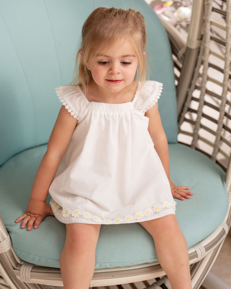 Little girl sitting on the swing chair wearing Organicline sleeveless natural white dress, featuring angle-sleeves with a line of lace eyelet on the edge and a gentle elastic neckline. Small yellow sunflowers embroidered at the end of the hem making this clean and simple dress a playful style.