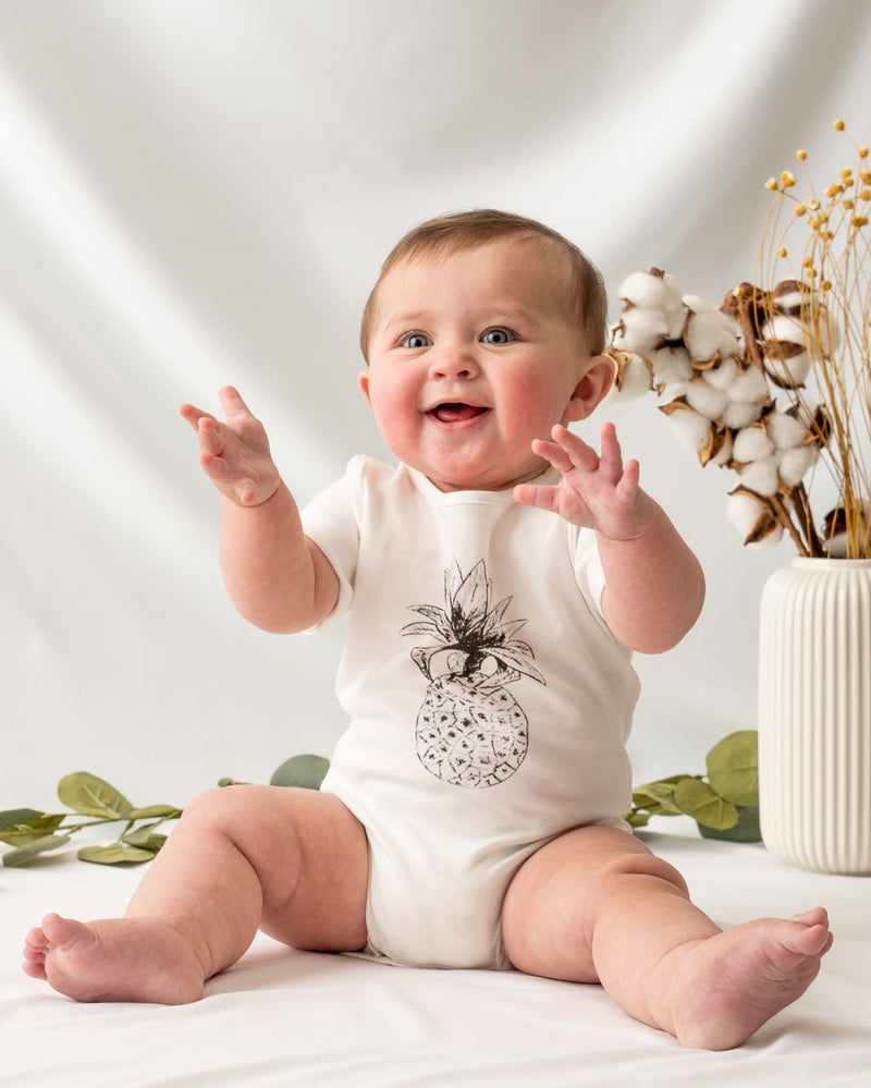 Short sleeve undyed natural white unisex baby bodysuit, featuring a hand-draw pineapple at the front and snap buttons on the left shoulder and the bottom for easy dressing and nappy changing.