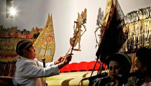 This image shows the Dalang in action. Shadow theaters are orchestrated by the Dalang (puppet master) who manipulates the puppets and creates the speech, accents and sounds according to age and gender of the character. The Dalang is also a composer, improviser, producer, orator, singer, choirmaster, dance master and stage manager.  The Shadow theater performance is accompanied by the unique sounds of the Javanese gamelan orchestra.