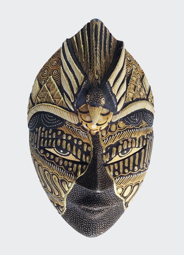 "This image shows magnificent art object is a Merak Prada Jewelry Container made of carved soft wood with painstakingly hand dye-painted multi-colored Batik motif inlaid with Prada (gold) highlights. The lid of the container is a mask carved and painted by a highly skilled artisan in Indonesia. The mask depicts a Peacock or Merak in the Indonesian language ""Bahasa Indonesia"". The container will enhance any living room decor, bedroom decor, kitchen decor, hallway. decor or office decor."