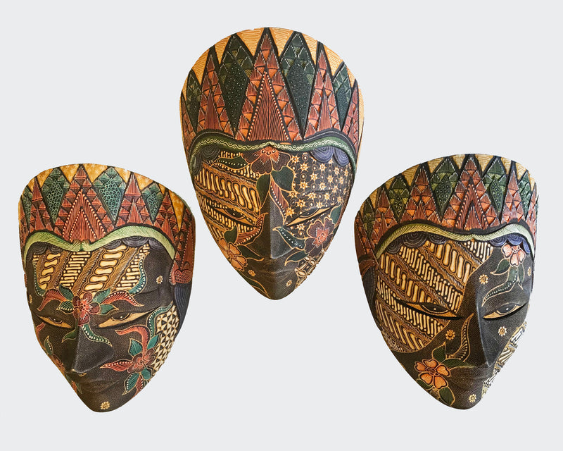This image shows a magnificent Wall Decor mask made of hand carved wood with intricately hand dye-painted colorful Batik motif tones. The Batik process creates a velvety cloth like texture over the entire surface. The mask is carved and painted by a highly skilled artisan in Indonesia. The mask will enhance any living room decor, bedroom decor, kitchen decor, hallway. decor or office decor.