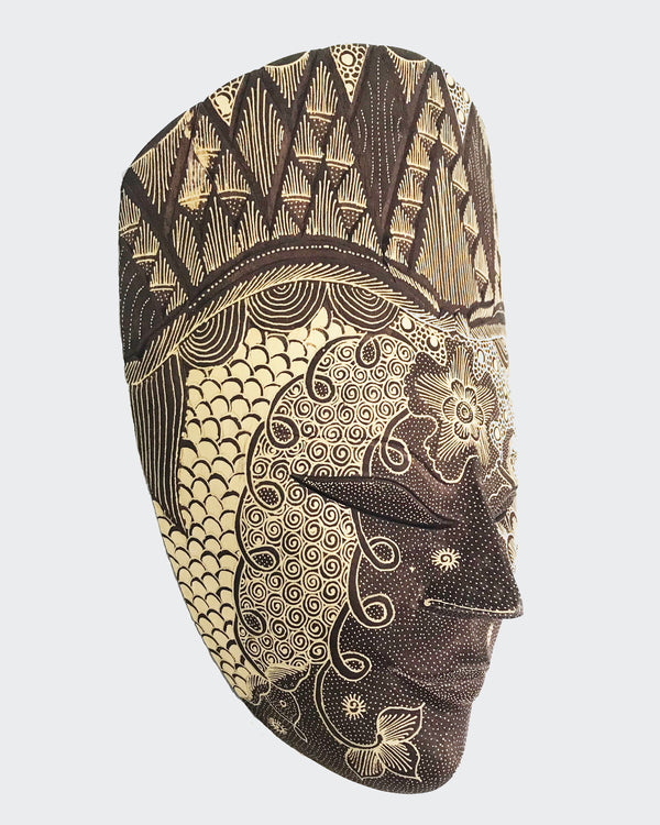 This image shows a magnificent Wall Decor mask made of hand carved wood with intricately hand dye-painted Batik motif colored in soft darker earth tones The Batik process creates a velvety cloth like texture over the entire surface. The mask is carved and painted by a highly skilled artisan in Indonesia. The mask will enhance any living room decor, bedroom decor, kitchen decor, hallway. decor or office decor.