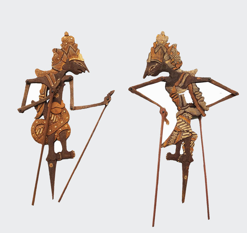 This image shows two ornamental Shadow Puppets Wayang Kayu (wooden Puppet) Rama and Shinta, and are entirely hand made. The bodies of the puppets are made of intricately carved albesla wood painted In soft earth tones. The Puppets are carved and painted by a highly skilled artisan in Indonesia. The Puppets will greatly enhance any living room decor, bedroom decor, kitchen decor, hallway. decor or office decor.
