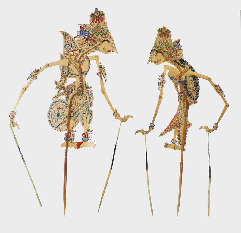 This image shows two Ornamental Puppet Batik Wayang Kulit Rama & Shinta Shadow PuppetsThe bodies of the puppets are made of intricately carved and colorfully painted water-buffalo leather. The Puppet is carved and painted by a highly skilled artisan in Indonesia. The center handle and manipulating rods are carved from the water buffalo horn. The Puppets will greatly enhance any living room décor, bedroom décor, kitchen décor, hallway. décor, or office décor.