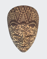This image shows a magnificent Wall Decor mask made of hand carved wood with intricately hand dye-painted Batik motif colored in soft earth tones. The Batik process creates a velvety cloth like texture over the entire surface. The mask is carved and painted by a highly skilled artisan in Indonesia. The mask will enhance any living room decor, bedroom decor, kitchen decor, hallway. decor or office decor.