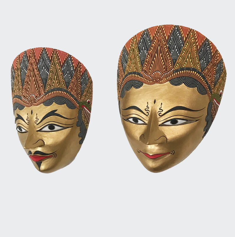 This image shows a magnificent Wall Decor wall-hanging and is a pair of masks, Rama & Shinta. They are made of hand carved Albesia wood with intricately hand dye-painted Batik motif and gold colored faces. These masks will enhance any living room decor, bedroom decor, kitchen decor, hallway. decor, or office decor.