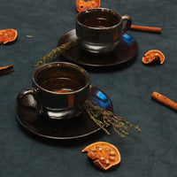 Two set of our cosmic glaze cup and saucer on a dark blue background with dried mango stems.