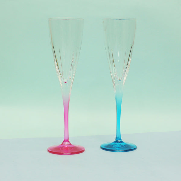Pink and blue champagne glasses placed on a dark blue background with decorative copper balls around them.