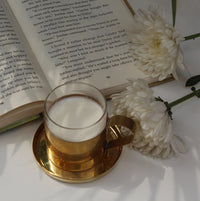 Brass and glass cup and saucer set placed next to a open book