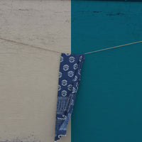 Our sustainable Indigo Mul (Flora) stole shot against a beige and blue wall.