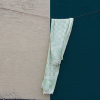 Our Mint Green Mul stole made with recycled mul and cotton shot against a beige and blue wall.