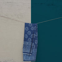 Our sustainable Indigo Mul (Chi) stole shot against a beige and blue wall.