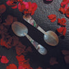 Two spoons made out of the rare black mother of pearl and the classic white mother of pearl placed on dark grey concrete with red flower petals around them.