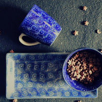 A serving tray with a bowl containing cereals and a mug placed next to it. All in cobalt blue color.
