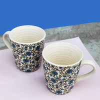 Blue cozy together mugs placed on a pink and blue background