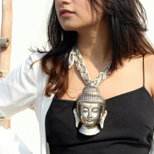 Silver buddha neckpiece with white and silver string worn by a woman
