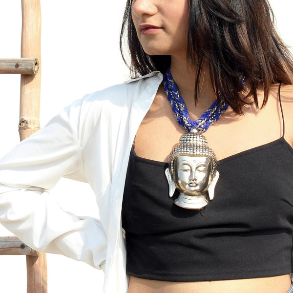 Silver buddha neckpiece with blue and silver string worn by a woman
