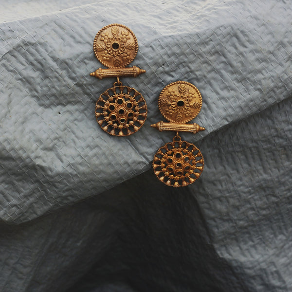 Our Charka earrings made with unpolished brass placed on a grey background.