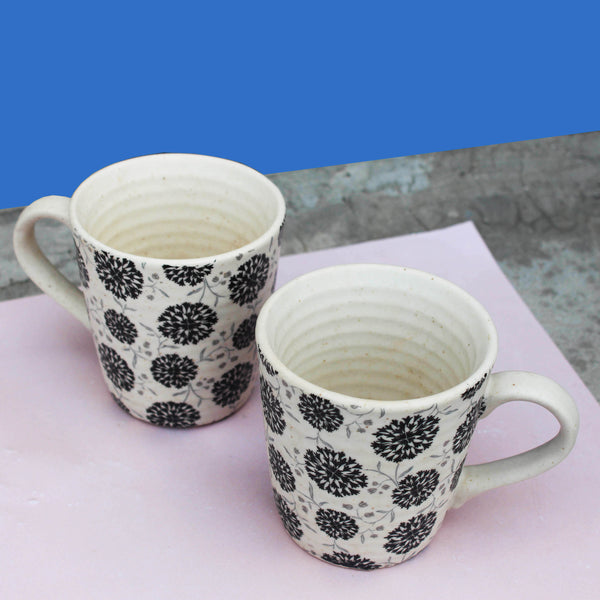 Floral Monochrome cozy together mugs placed on a brown background