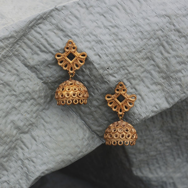 Our Classic Jhumka earrings made with unpolished brass placed on a grey background.