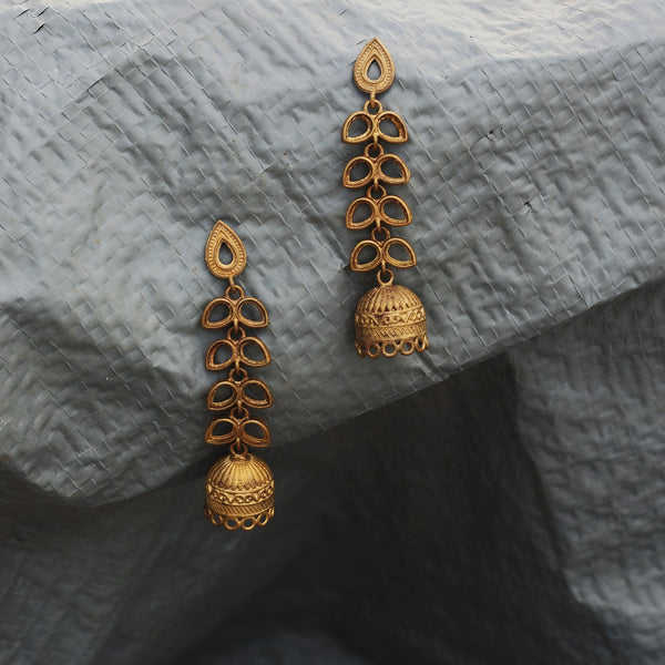 Our Latkan earrings made with unpolished brass placed on a grey background.