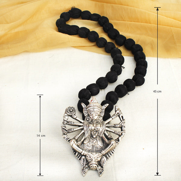 Silver kali neckpiece with black beaded string worn by a woman