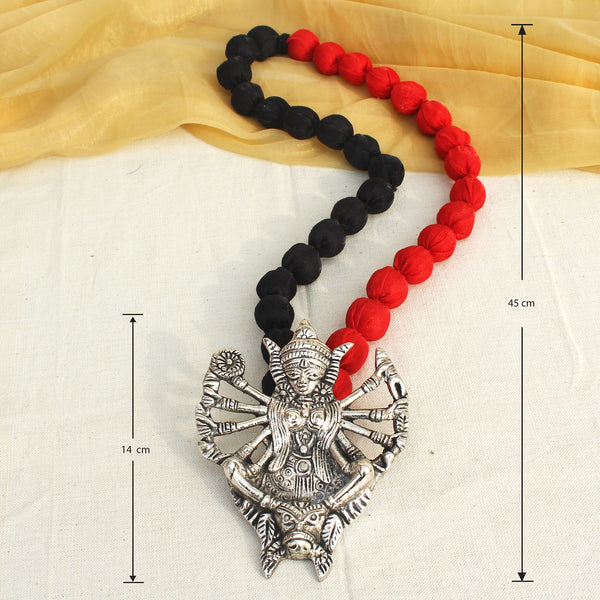Silver kali neckpiece with black and red beaded string worn by a woman